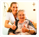 caregiver and elder showing thumbs up